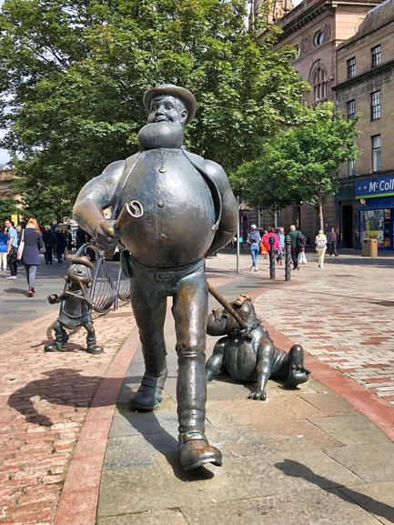 Desperate Dan and Minnie the Minx sneaking up behind him