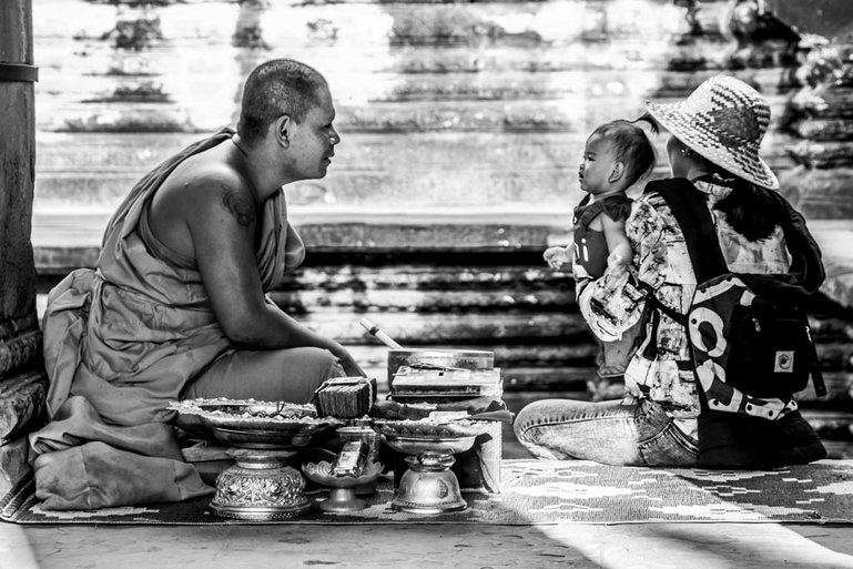 A young child receives a blessing from a Buddhist monk inside Angkor Wat