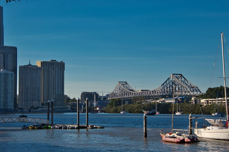 Yachts line the Brisbane River as it winds under the Story Bridge