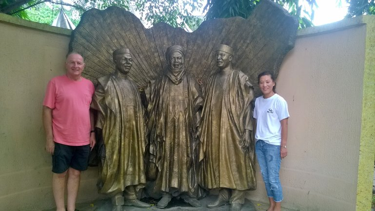 Tourist Posing with a monument of The Three Nigerian tribes at the Old Prison  yard now called The Freedom Park Lagos